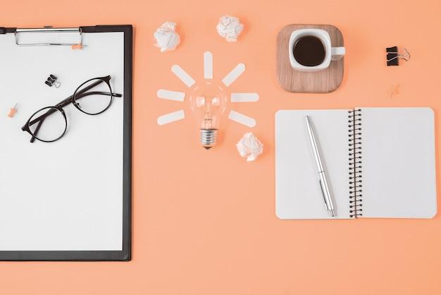 Financiële planning brainstormen rommelige afbeelding van de tabel top met lege klembord op oranje achtergrond.