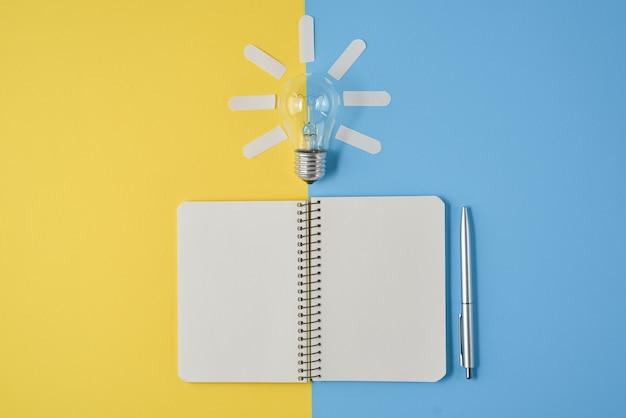 Financiële planning tafelblad met pen, kladblok, gloeilamp op gele en blauwe achtergrond.