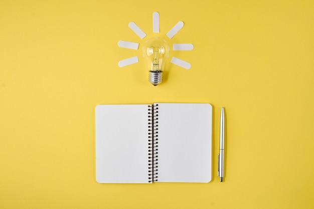 Financiële planningstafelbovenkant met pen, blocnote, gloeilamp op gele achtergrond.
