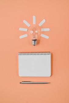 Financiële planningstafelbovenkant met pen, blocnote, gloeilamp op oranje achtergrond.