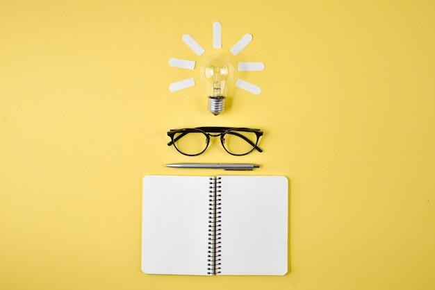 Financiële planningstafelbovenkant met pen, blocnote, oogglazen en gloeilamp op gele achtergrond.
