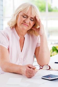 Financiële problemen. gefrustreerde senior vrouw leunt haar hoofd bij de hand en houdt de ogen gesloten terwijl ze aan tafel zit met rekeningen en rekenmachine erop