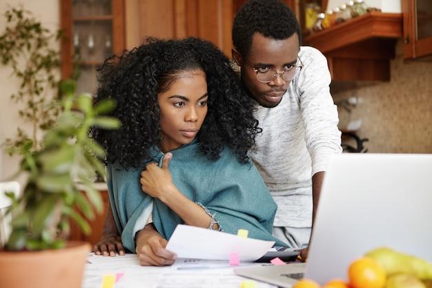Financiële problemen, gezinsbudget en schulden. gefrustreerde jonge afrikaanse man en vrouw laptop pc gebruiken terwijl ze samen papierwerk doen, kosten berekenen, rekeningen in hun moderne keuken beheren