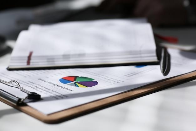 Financiële statistiekendocumenten op klembordstootkussen