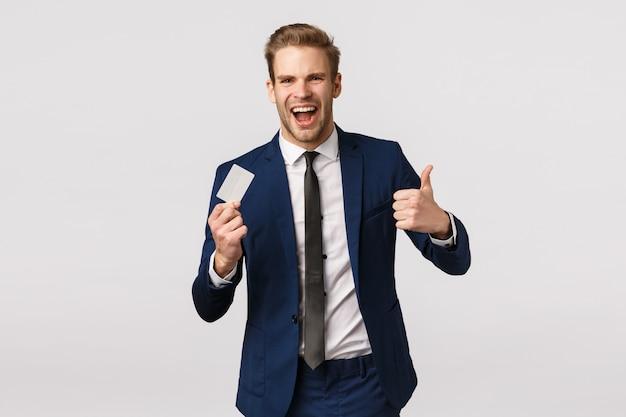 Financiën, bedrijfsleven en rijkdom concept. vrolijke knappe jonge blonde zakenman die duim-omhoog in goedkeuring, zoals de creditcard van de gebarengreep tonen, bankdienst aanbevelen, aankoop doen