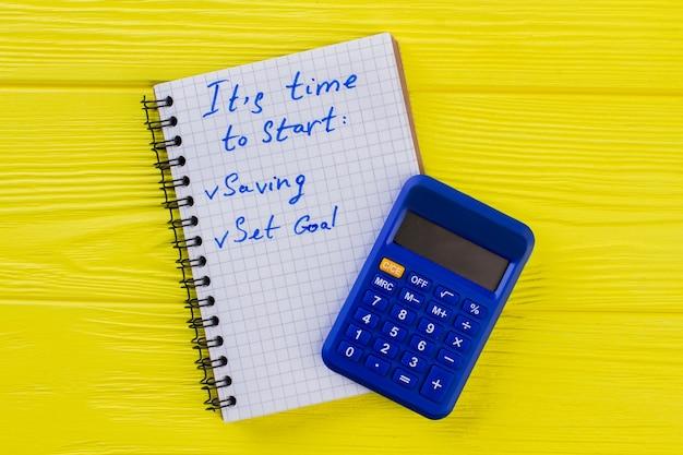 Financiën en boekhoudconcept. rekenmachine met kladblok op geel hout.