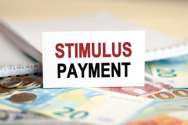Financiën en economie concept. op de tafel liggen rekeningen, een bundel dollars en een bord waarop het is geschreven - stimulus betaling
