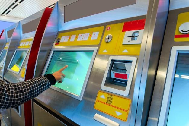Financiën, geld, bank en mensenconcept - sluit omhoog van hand die pincode ingaan bij atm-machine