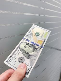 Financiën geld. mens die honderd dollarsrekening houdt