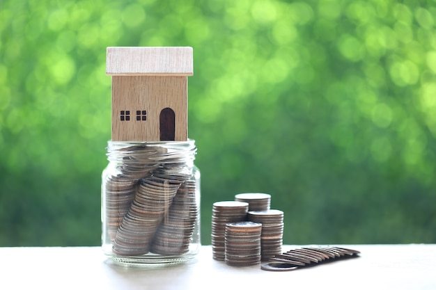 Financiën, modelhuis op muntstukkengeld in glasfles op aard groene achtergrond, geld besparen voor nieuw huisconcept