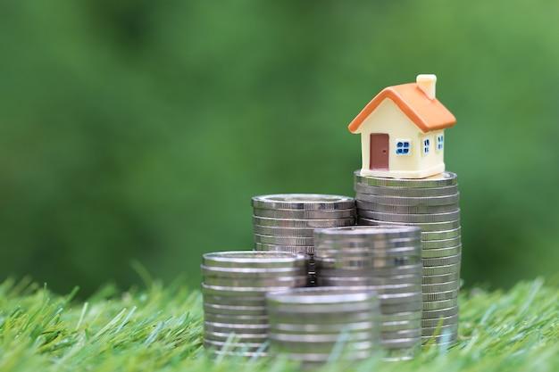 Financiën modelhuis op stapel muntstukkengeld op natuurlijke groene ruimte
