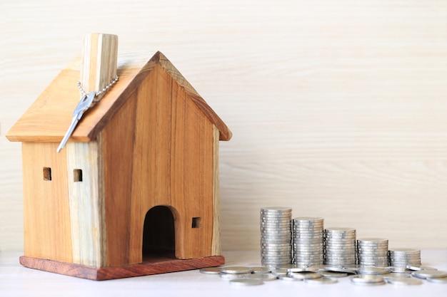 Financiën, stapel muntstukkengeld en modelhuis op wit