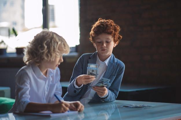 Financiën. twee jongens die geld tellen en er druk uitzien