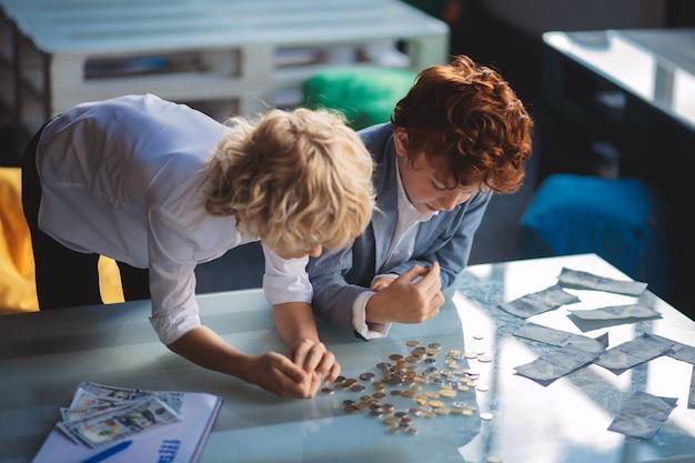 Financiën. twee jongens tellen geld en kijken betrokken