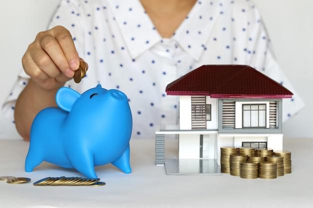 Financiën, vrouwenhand die muntstukken in spaarvarken met modelhuis op witte achtergrond zetten, geld voor nieuw huisconcept besparen