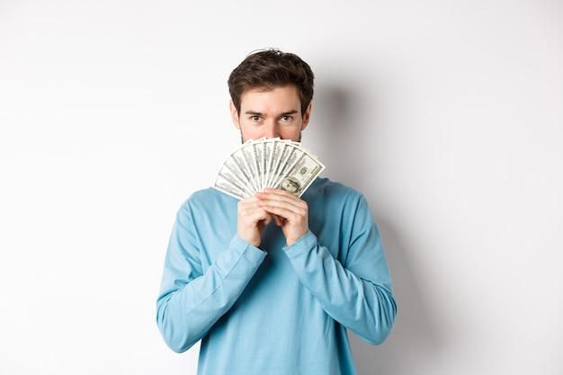 Financiënconcept. glimlachende jonge man die gezicht achter geld bedekt, dollars toont en er gelukkig uitziet, staande op een witte achtergrond.