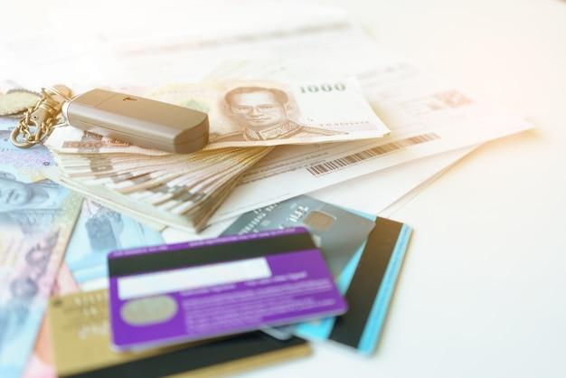 Financiënconcept: thaise bankbiljetten, rekeningen, creditcards en autosleutel voor betaling