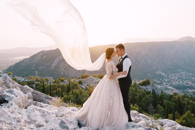 Fineart bestemming trouwfoto in montenegro berg lovchen het bruidspaar knuffelt bovenop de