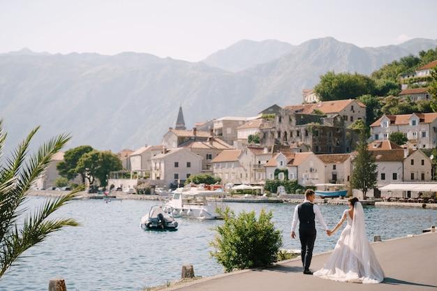 Fineart trouwfoto in montenegro perast een bruidspaar loopt langs de boulevard bij de zee