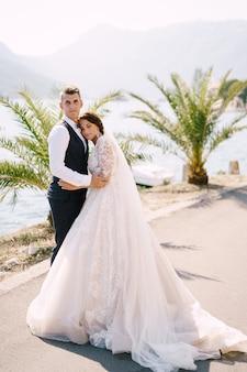 Fineart trouwfoto in montenegro perast een bruidspaar staat omhelzend op de kade in de buurt