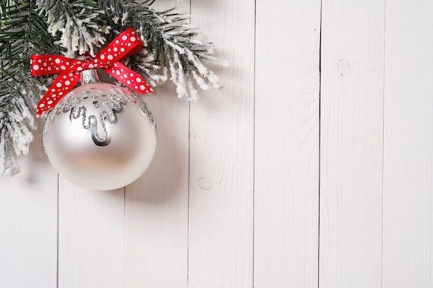 Fir kerstboom en ornament met rood lint op een houten bord