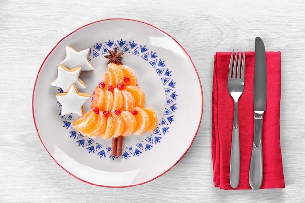 Fir kerstboom gemaakt van mandarijnen, op plaat, close-up