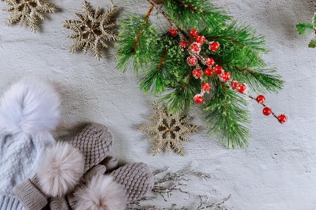 Fir kerstboom met rode bessen en wanten met hoed