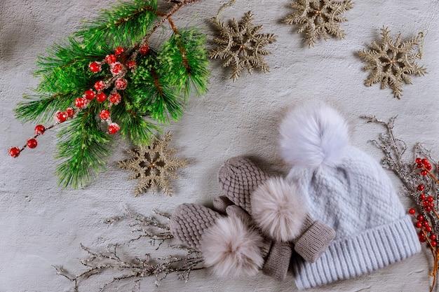 Fir kerstboom met rode bessen, sneeuwvlokken en wanten met hoed