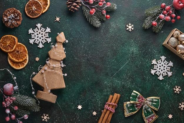 Fir kerstboomtakken, kerstballen, geschenkdoos, houten sneeuwvlokken en sterren op groene betonnen stenen achtergrond voor uw kerstgroeten. bovenaanzicht met kopie ruimte. kerst wenskaart.