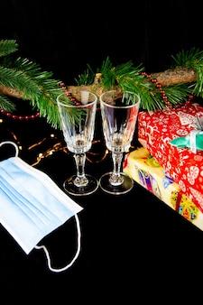 Fir tree branch versierd met kerstverlichting, geschenken, medisch masker en champagneglazen