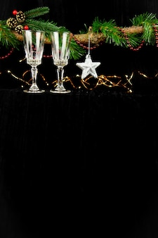 Fir tree branch versierd met kerstverlichting, zilveren ster en champagneglazen