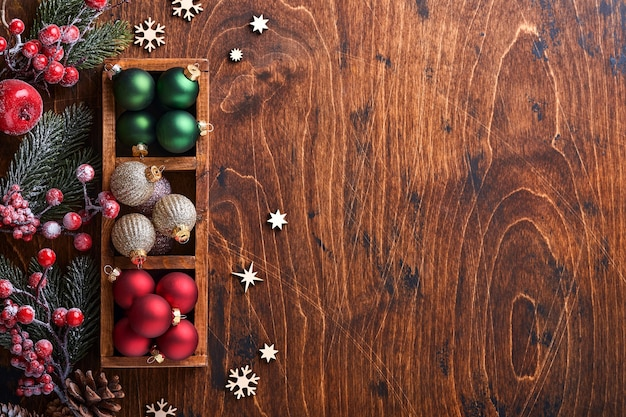 Fir tree decor rode en groene kerstballen, gevormde kaneel en droge sinaasappelschijfjes op hout achtergrond voor uw kerstgroeten. bovenaanzicht met kopie ruimte. kerst wenskaart.