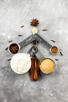 Fir-tree gemaakt van ingrediënten voor kerstkoekjes op een grijze achtergrond.
