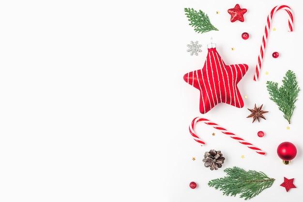 Fir tree takken rode decoraties snoep dennenappels op witte achtergrond