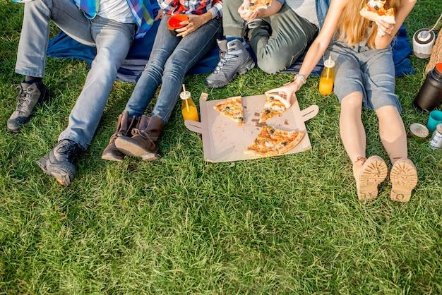 Firends eten pizza zittend op het gras. uitzicht van bovenaf op de poten en pizza