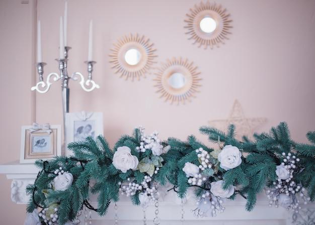 Firslinger met kerstmisspeelgoed ligt op een witte open haard