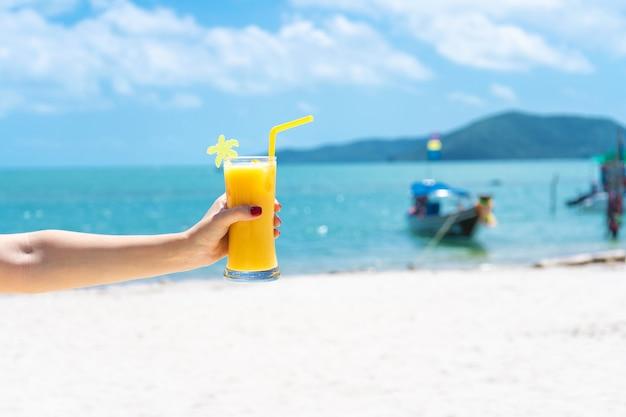 First-person view. het meisje houdt een glaskop koude mango vers op de muur van een tropisch zandstrand. wit zand en een boot. sprookjesvakantie in thailand