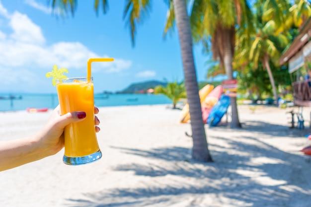 First-person view. het meisje houdt een glaskop van koud mango vers zand tropisch strand. wit zand en palmbomen. sprookjesachtige vakantie