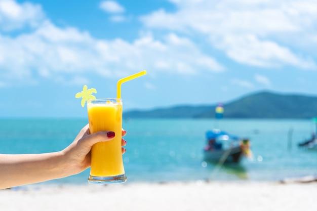 First-person view. het meisje houdt een glaskop van koude mango vers, een tropisch zandstrand. wit zand en een boot. sprookjesvakantie in thailand