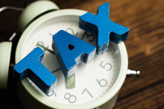 Fiscale alfabet en vintage wekker op hout
