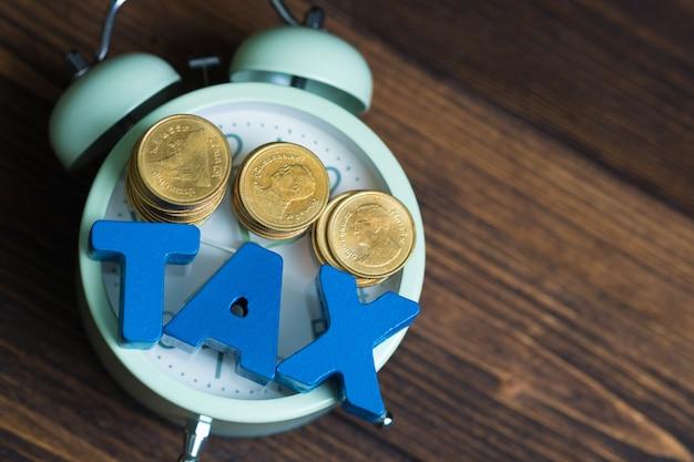 Fiscale alfabet met stapel munt en vintage wekker