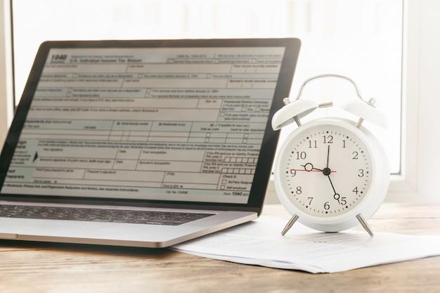 Fiscale tijd concept. laptop met formulier individuele aangifte inkomstenbelasting met wekker