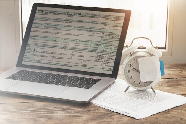 Fiscale tijd concept. laptop met formulier individuele inkomstenbelastingaangiftes met lege post-it op wekker