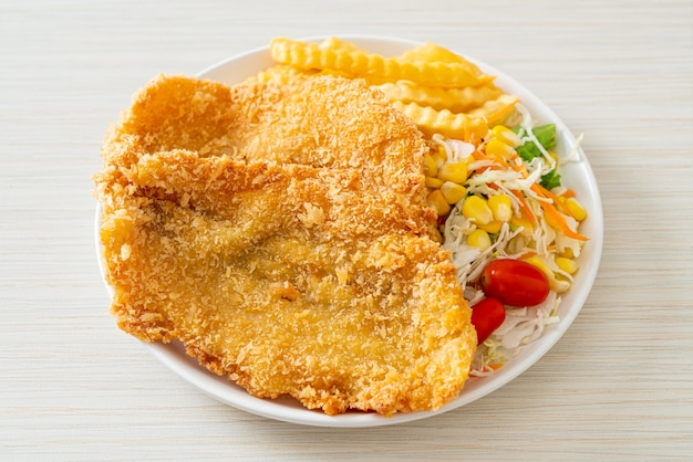 Fish and chips met minisalade op wit bord
