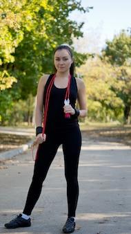 Fit aantrekkelijke vrouw in sportkleding staande met een rood springtouw gedrapeerd om haar nek in een park