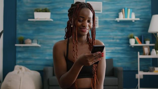 Fit atheltic vrouw met zwarte huid dragen sportkleding zittend op yoga swiss ball