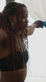 Fit atleet vrouw met donkere huid die spieroefeningen doet met fitness dumbbells