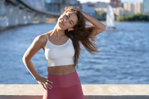 Fit atletische vrouw uitrekkende nek, warming-up training voor nekspieren buiten