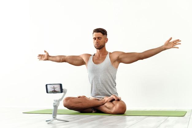 Fit blanke man die een blog opneemt of yoga-workout streamt