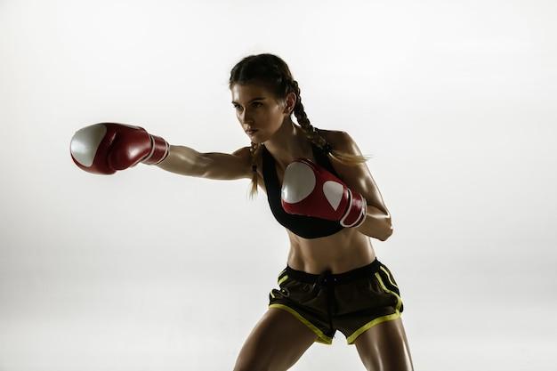 Fit blanke vrouw in sportkleding boksen geïsoleerd op een witte achtergrond.